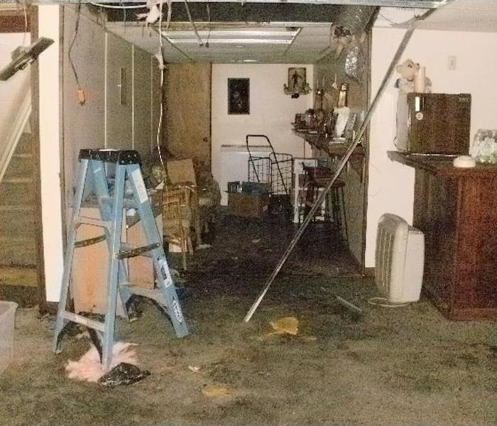 Dirty smoke residues and damaged furniture in the basement of a home.