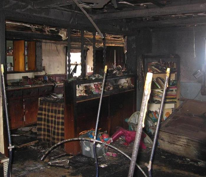 Extensive soot and a completely destroyed living room and kitchen area due to a fire.