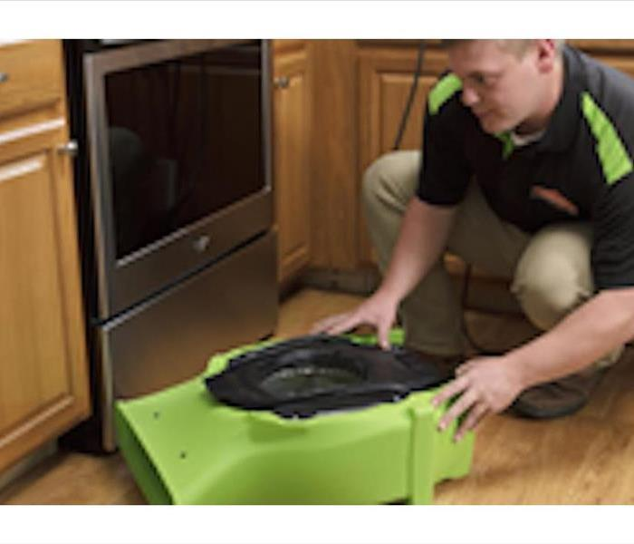 A SERVPRO professional using equipment to dry up water in a customer